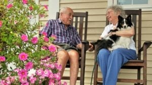 Couple sitting in rocking chairs discussing the cost of senior living